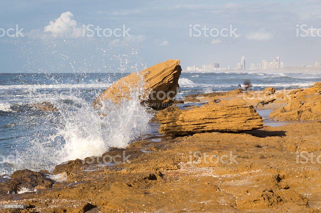 Beach sea wave splash cityscape buildings stone shore. stock photo