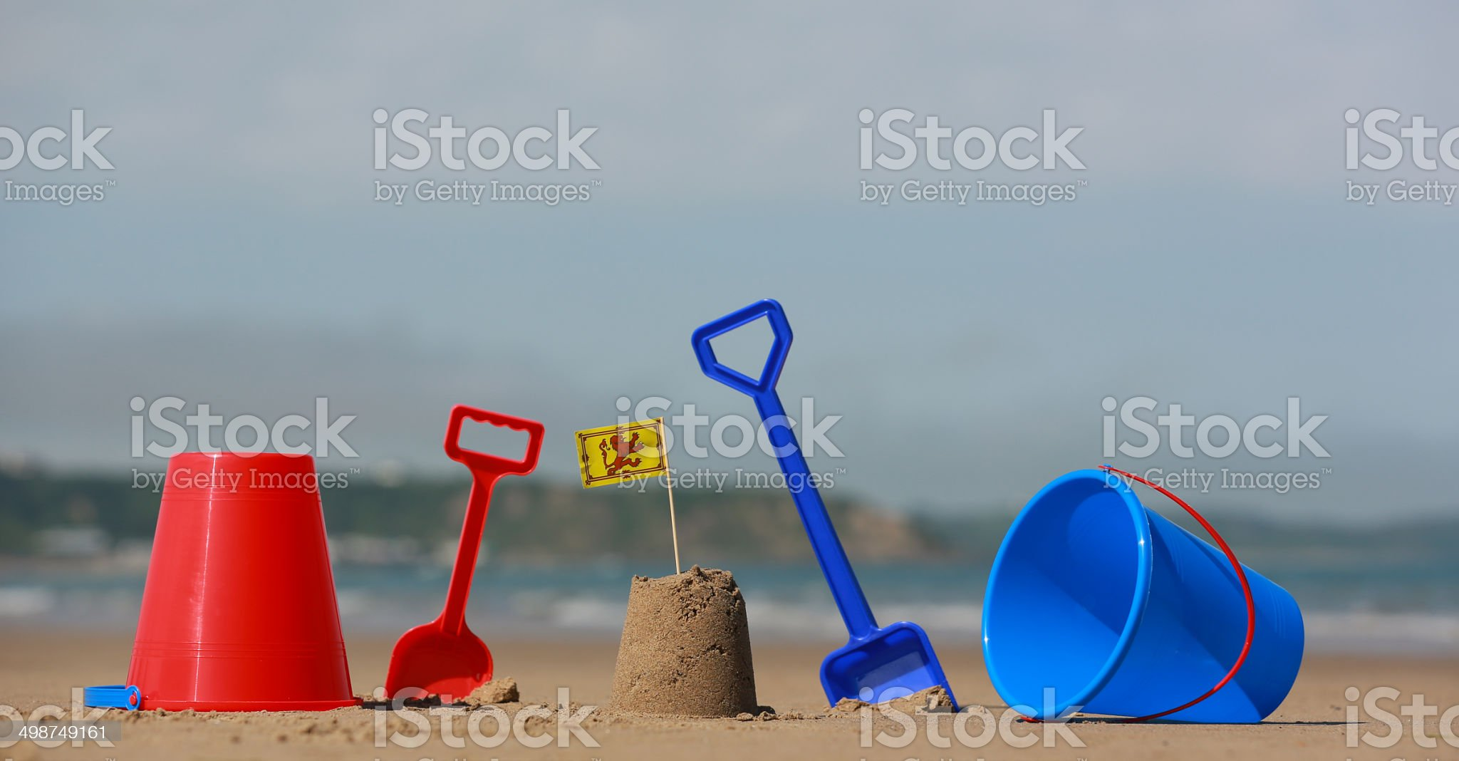 Beach, sea with buckets spades sandcastles and welsh flag royalty-free stock photo