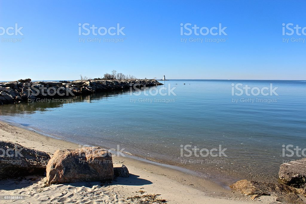 Beach side view of sea wall and lighthouse stock photo