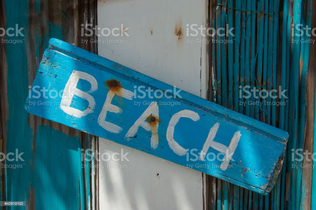 Beach sign on driftwood stock photo