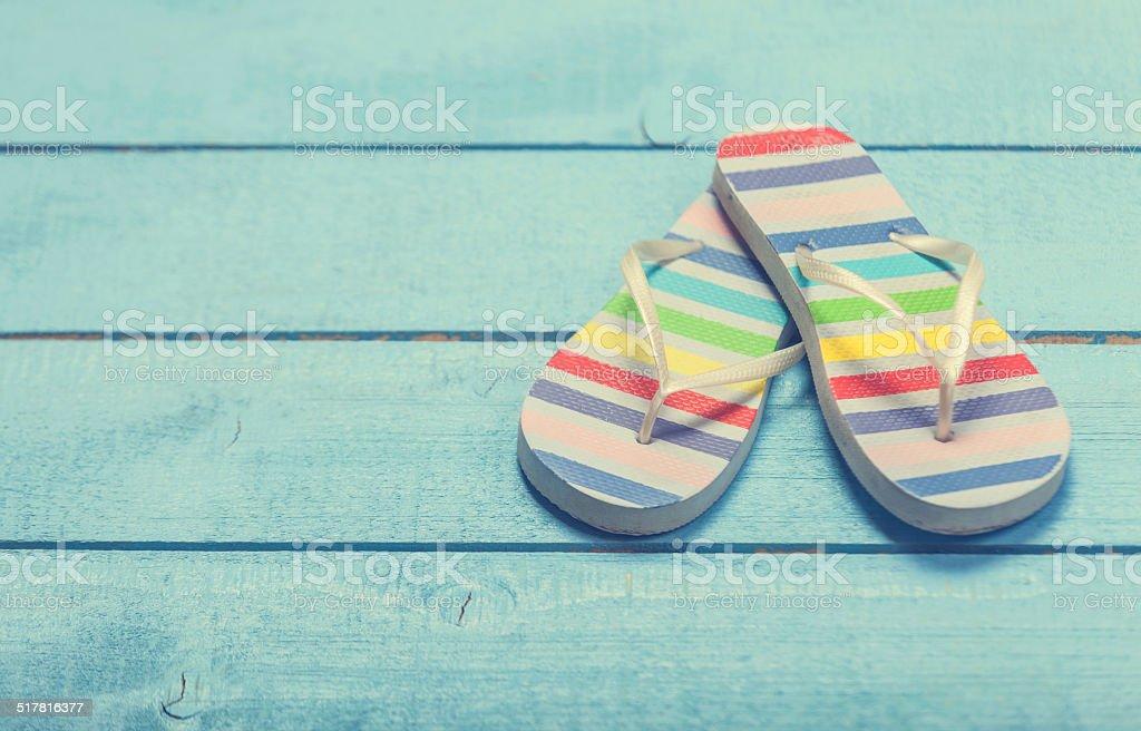 beach slippers on blue wood stock photo