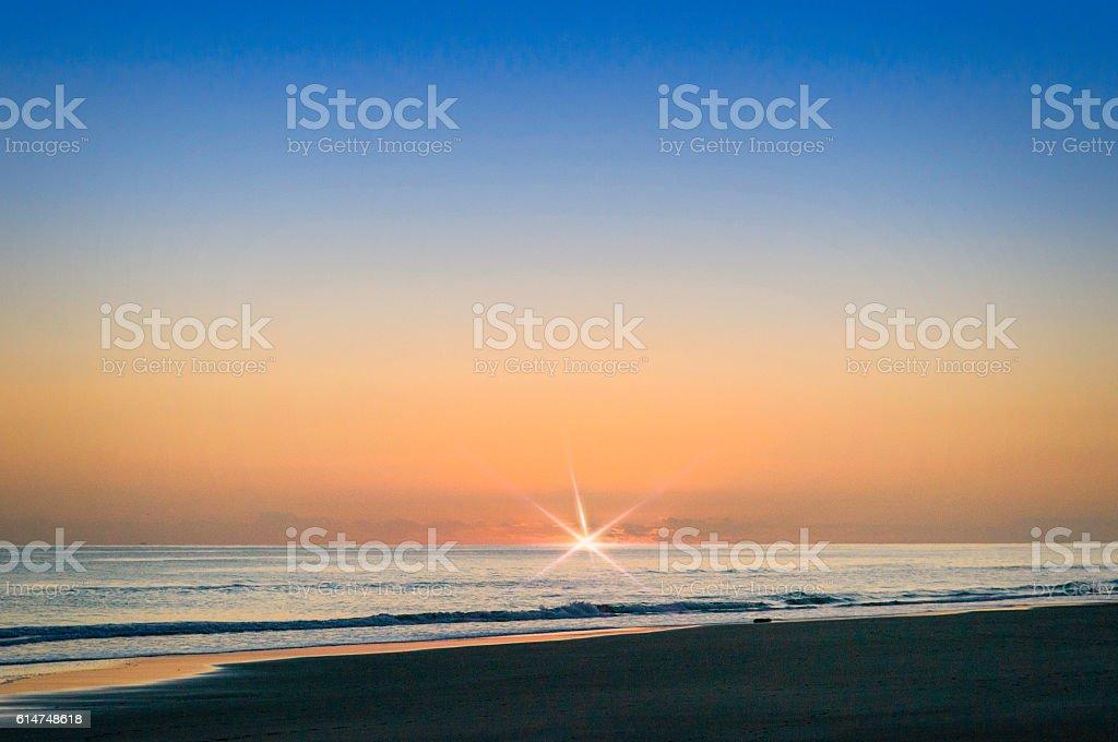 Beach sunrise with flare stock photo
