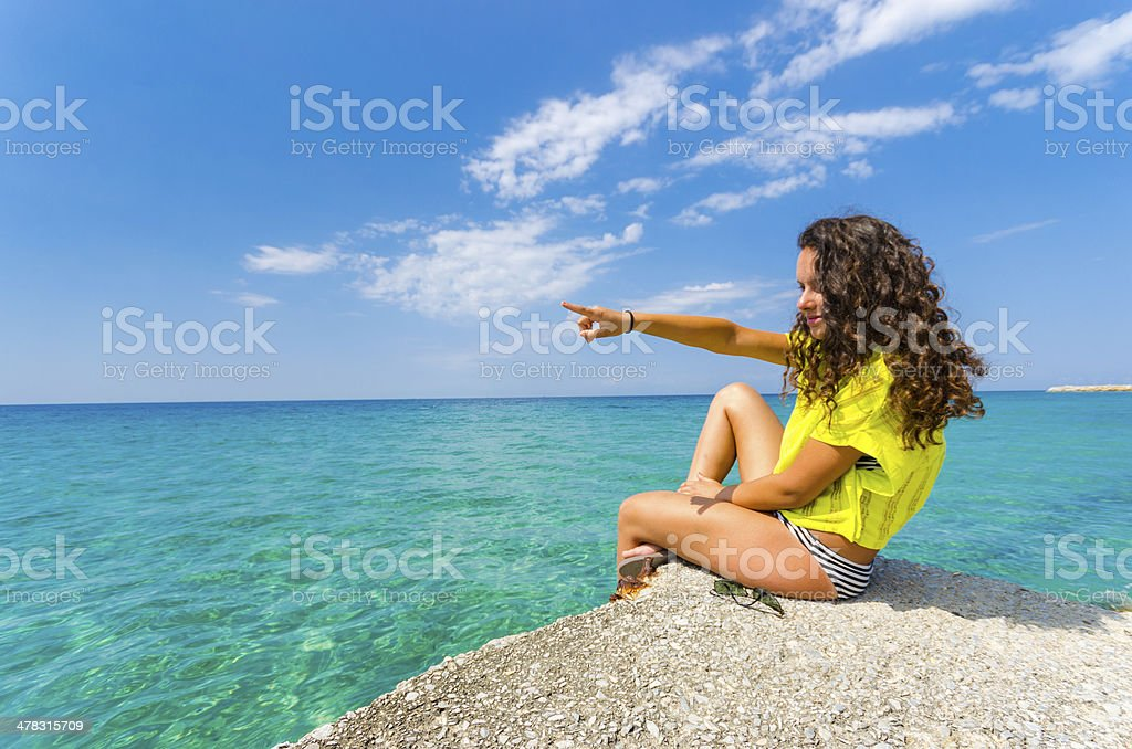 Beach teen woman with curly hair pointing ocean water horizon royalty-free stock photo
