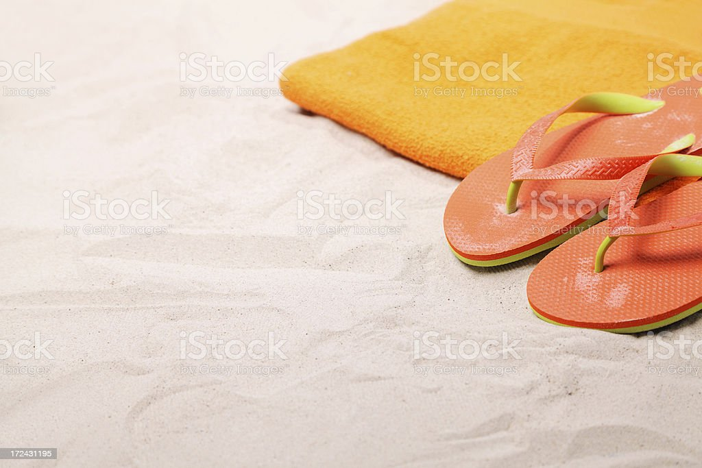 Beach towel and sandals on white sand royalty-free stock photo