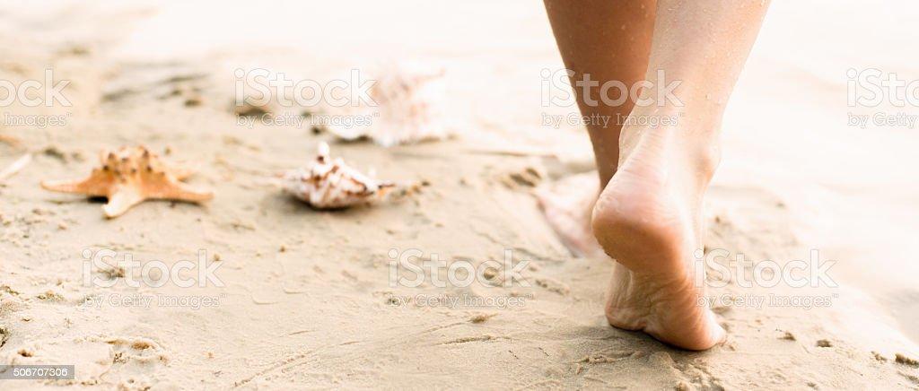Beach travel - woman walking stock photo