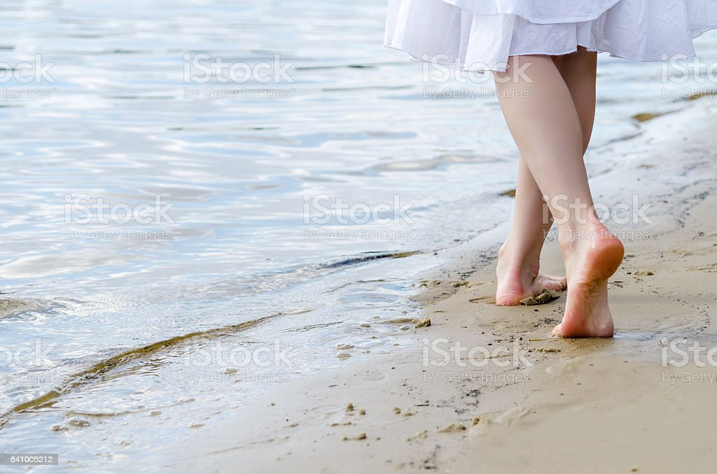 Beach travel - woman walking stock photo