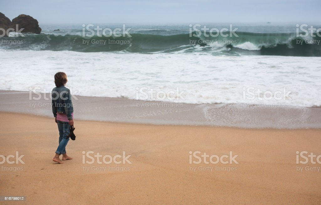 Beach travel - Young woman walking alone on the deserted coast of the Atlantic Ocean, Portugal stock photo