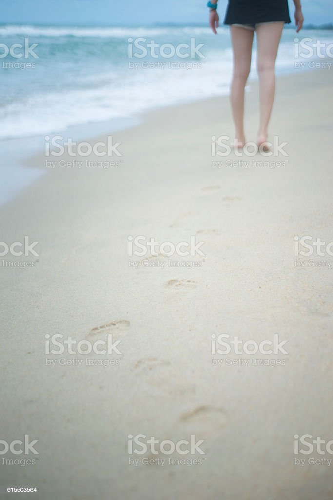 Beach travel - young woman walking on sand beach stock photo