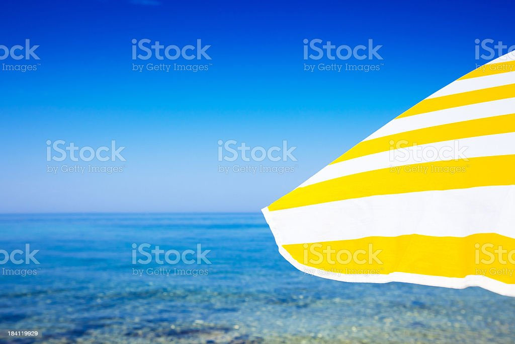Beach umbrella against blue morning sky and sea stock photo