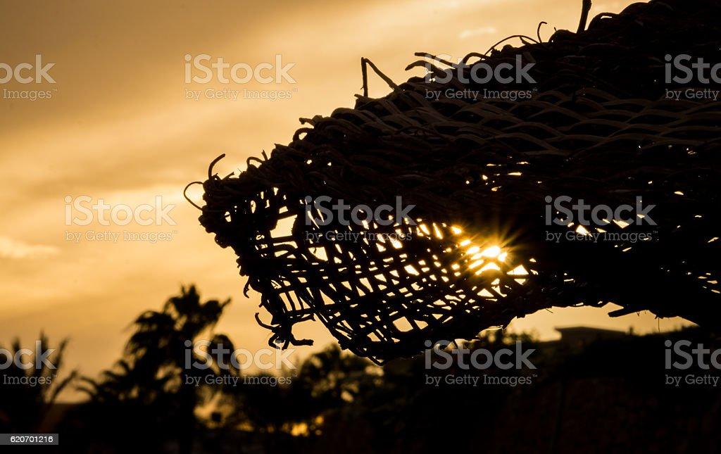 Beach umbrella in the sun at sunset stock photo