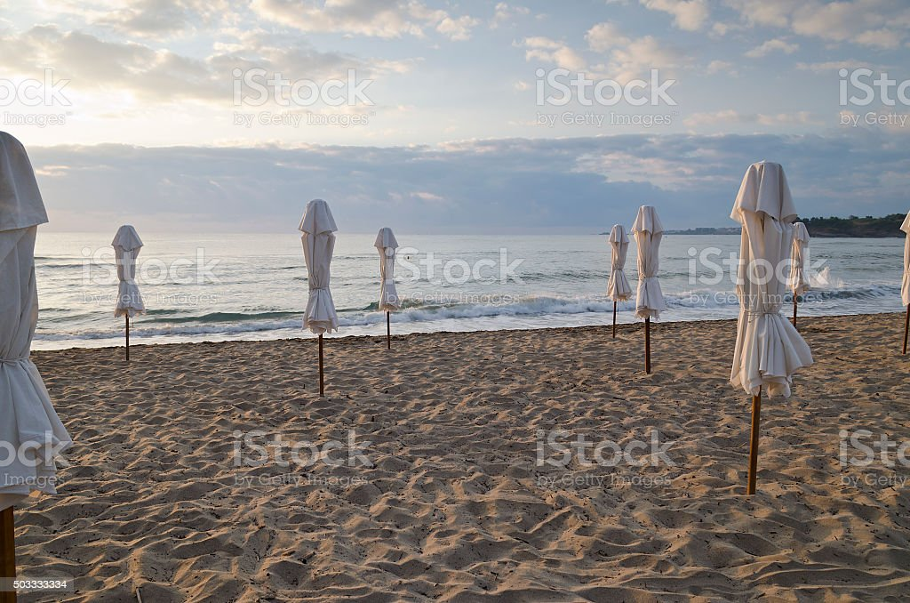Beach umbrella on deserted coast sea at sunrise stock photo