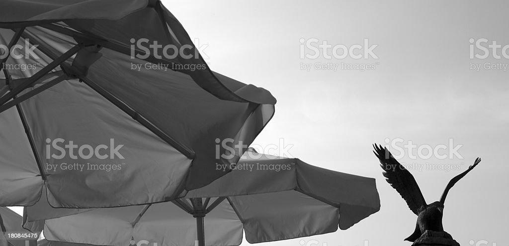 Beach umbrella with eagle statue royalty-free stock photo