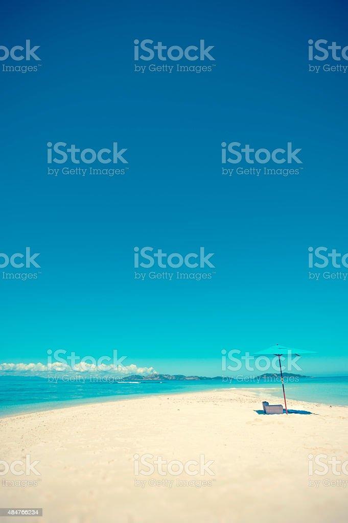 Beach umbrella with picnic on a remote sand island beach. stock photo