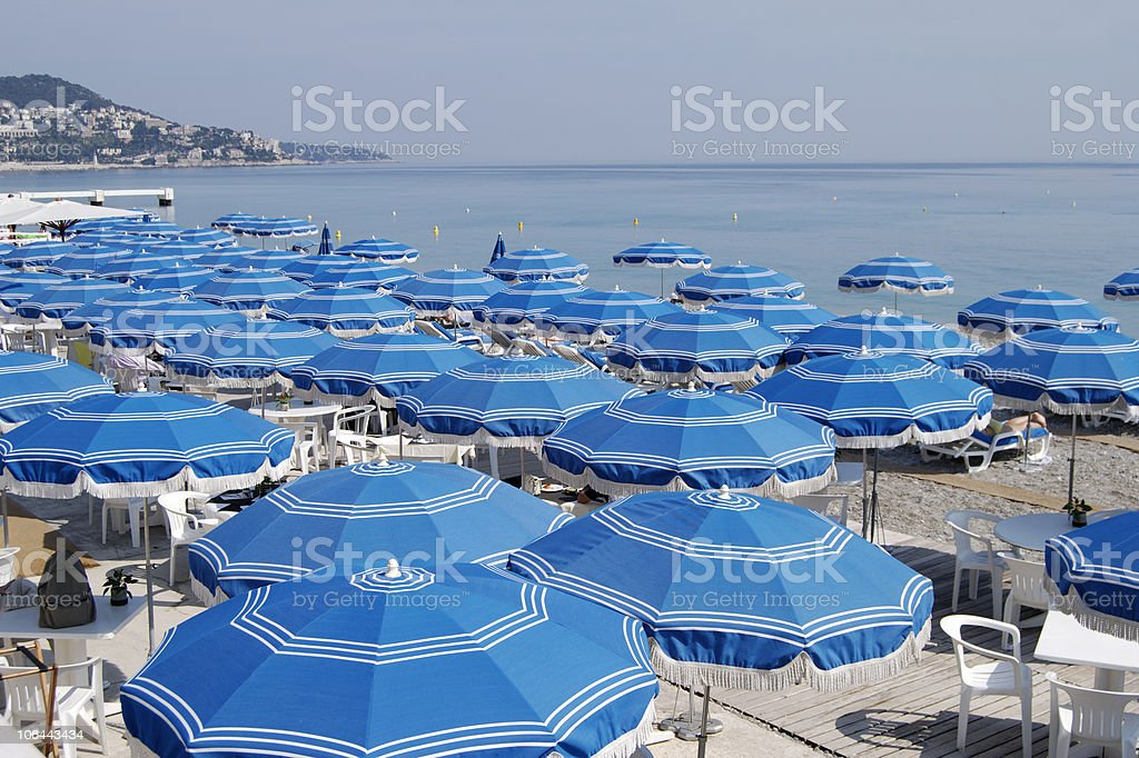 Beach umbrellas at Nice. Cote d'Azur. France royalty-free stock photo