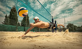 Beach volleyball player in action at sunny day under sky.