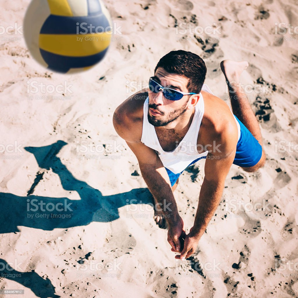 Beach volleyball player receiving the ball, action shot
