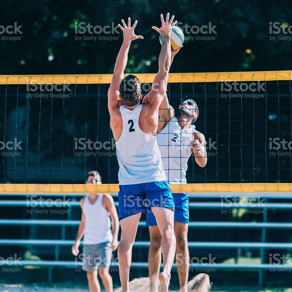 Beach volleyball players in action stock photo