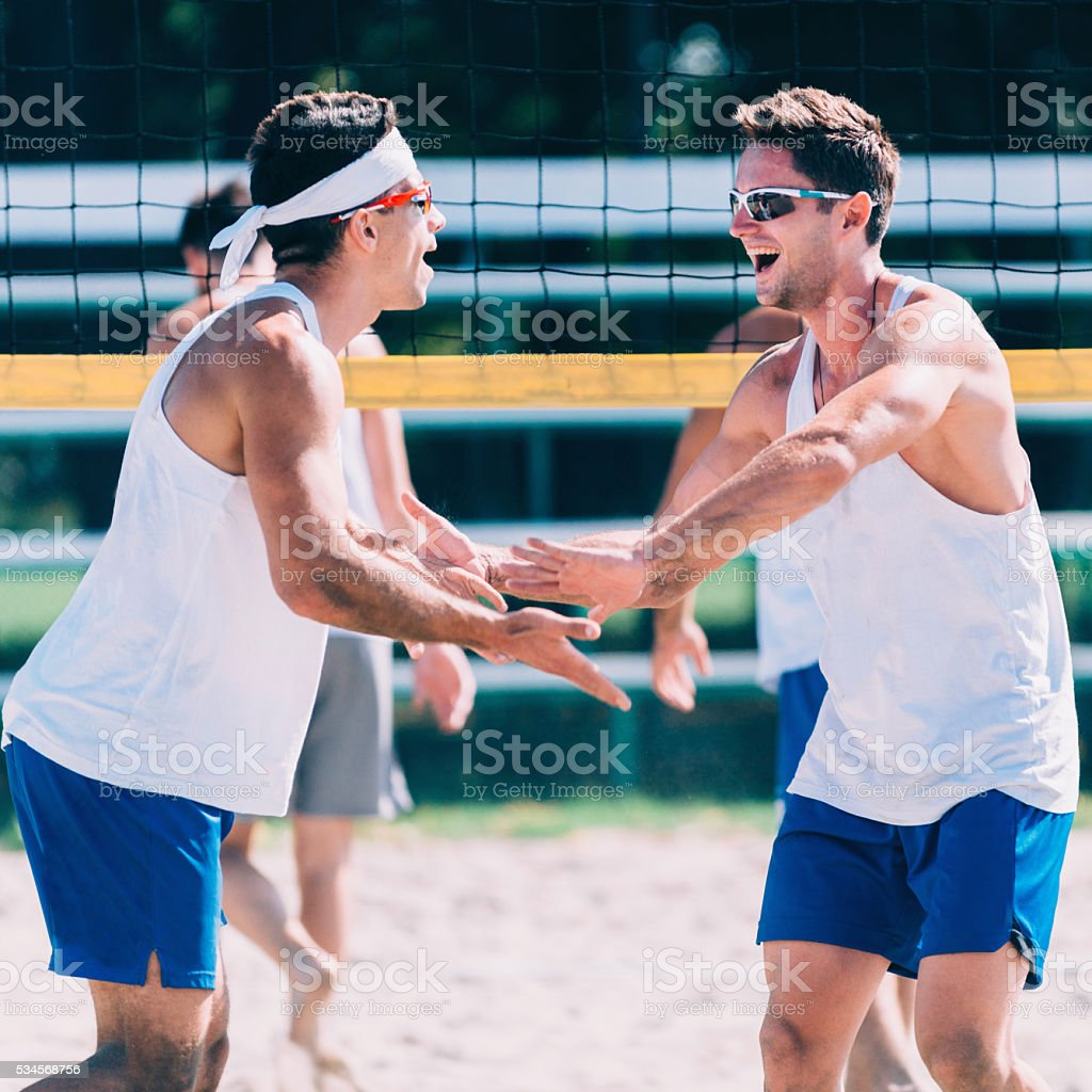 Beach volleyball team celebrating a point stock photo