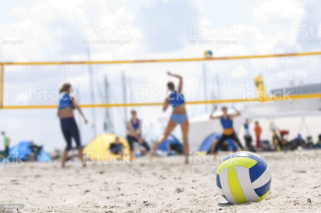 Beach Volleyball with closeup of ball in foreground royalty-free stock photo