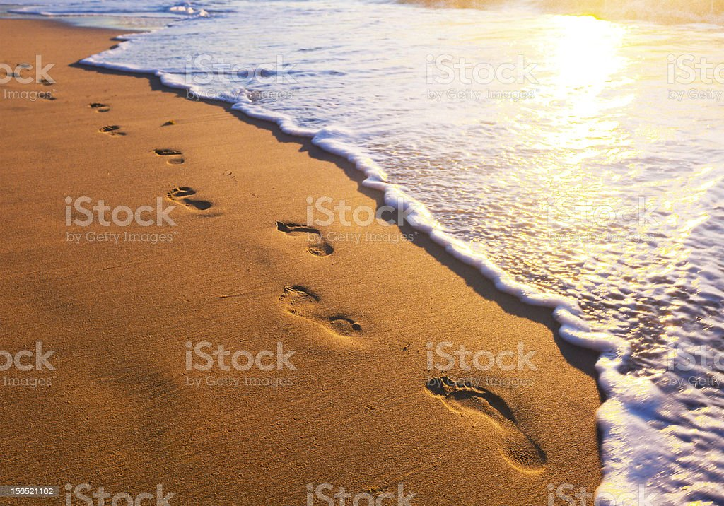 beach, wave and footsteps at sunset time stock photo