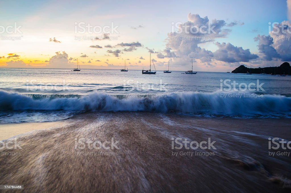 beach wave at sunset with distant yachts stock photo