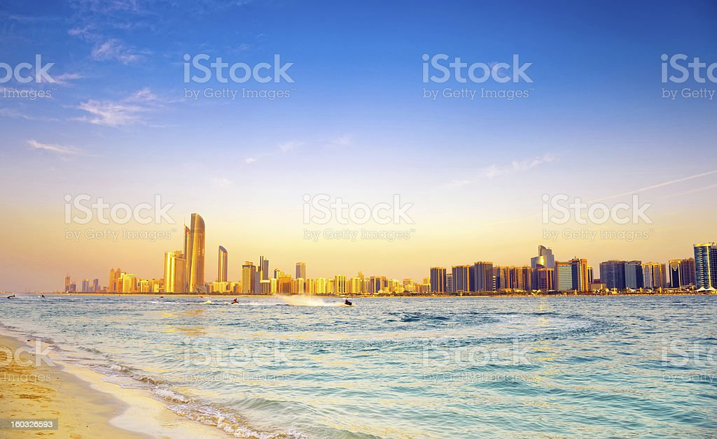 Beach with backdrop of Abu Dhabi skyline at sunset stock photo