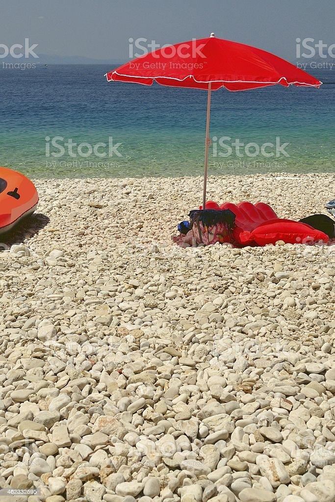 Plaża z otoczaki i czerwony Parasolka od słońca na lato dzień zbiór zdjęć royalty-free