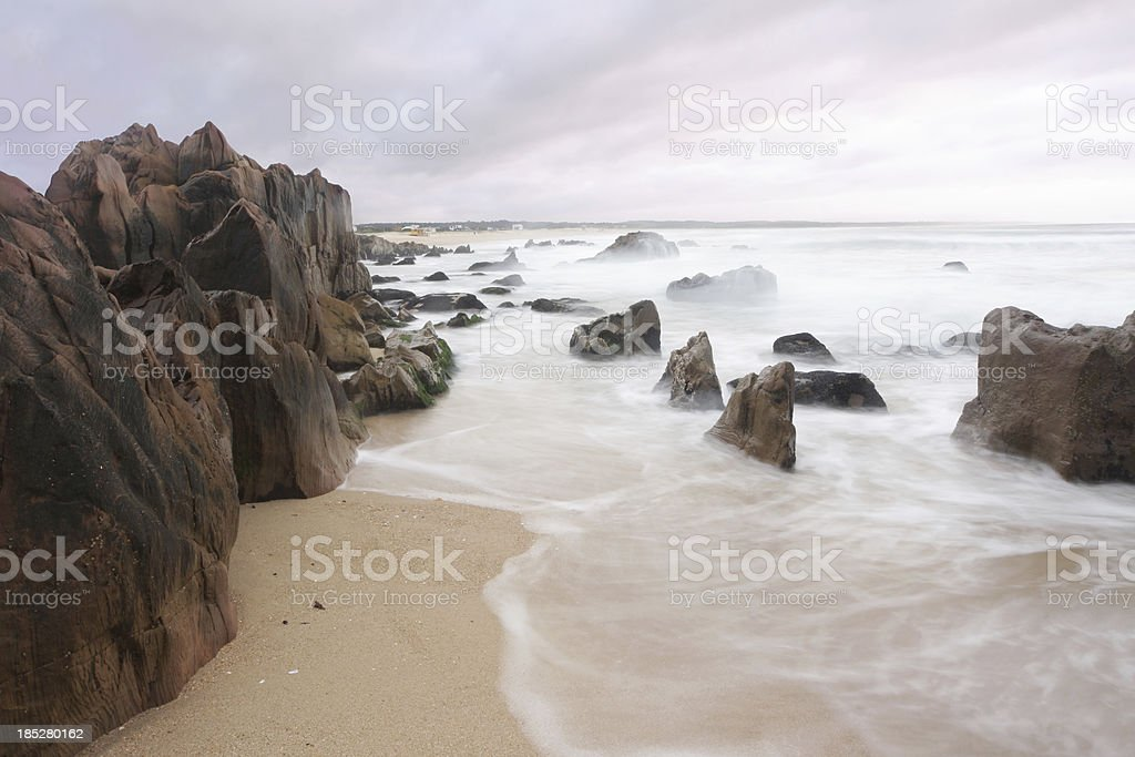Beach with rocks and blurry waves at sunset stock photo