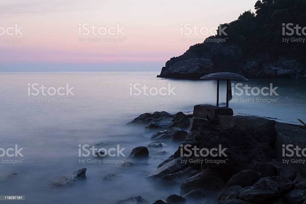Beach with rocks at sunset stock photo