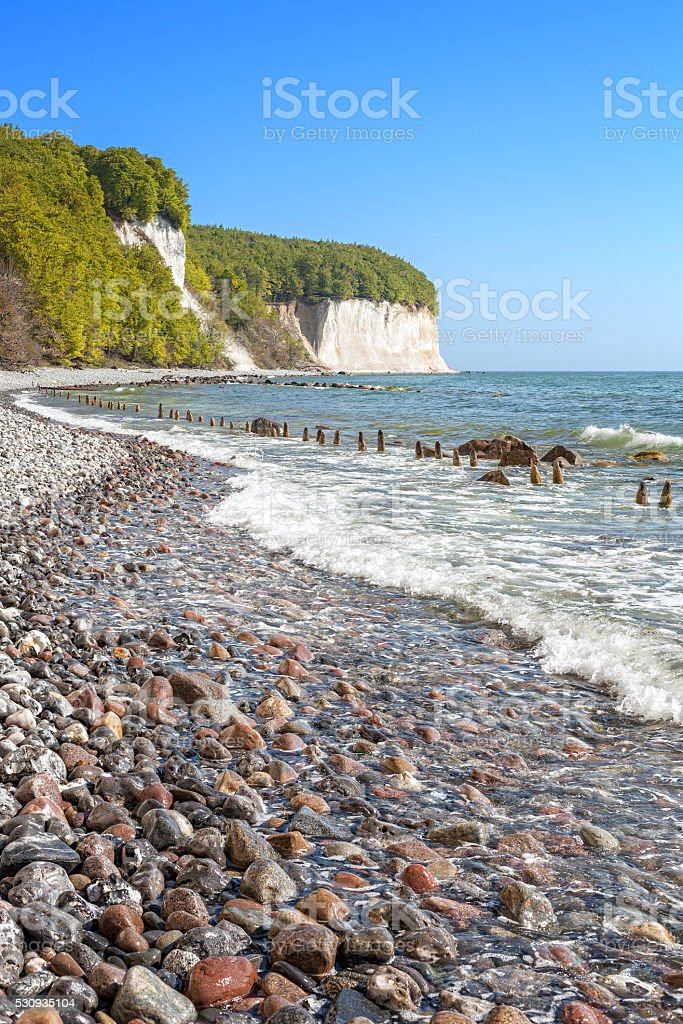 Beach with stones and chalk cliffs in distance. stock photo