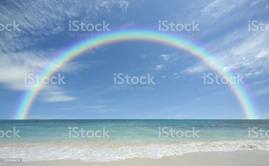 beach with sun and rainbow stock photo