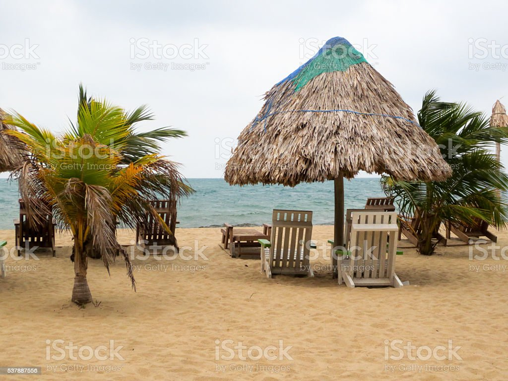 Beach with thatched umbrella in Placencia, Belize stock photo