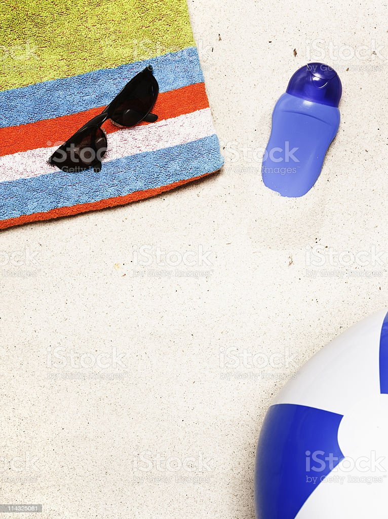 Beach with towel, sunglasses, sun screen, ball and copy space royalty-free stock photo