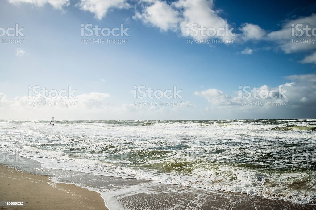 Beach with Windsurfer in the Waves royalty-free stock photo