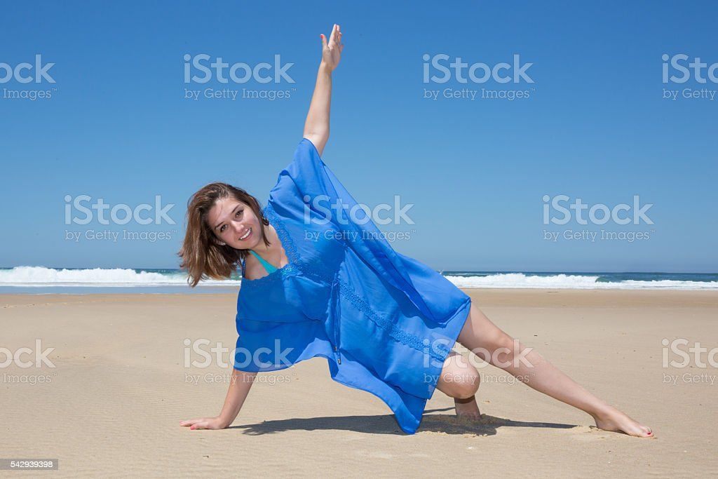 Beach Yoga smiling beautiful sporty young woman working out stock photo
