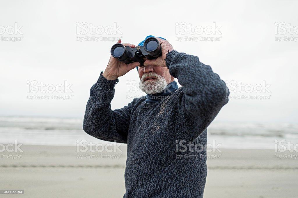 Beachcomber on the beach looking with binocular. stock photo