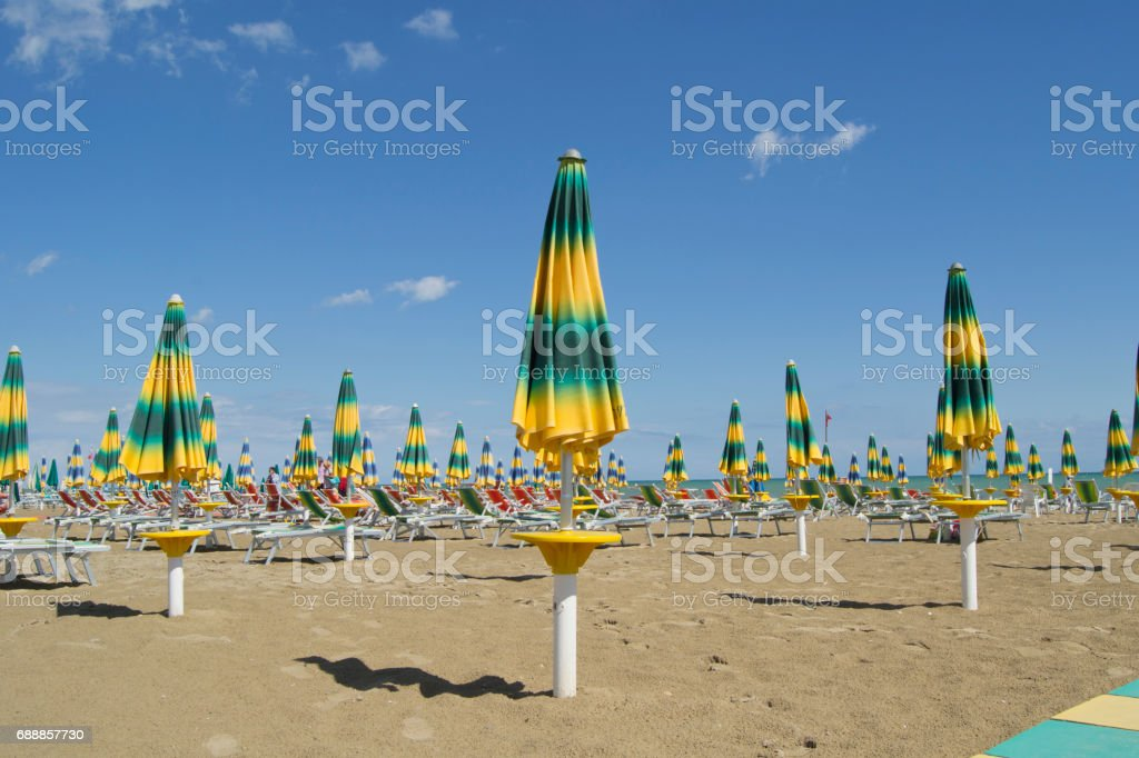 beache umbrellas with beach chairs at the end of the summer season stock photo
