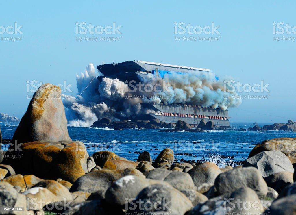 Beached barge ship deplosion at sea  near rocks stock photo