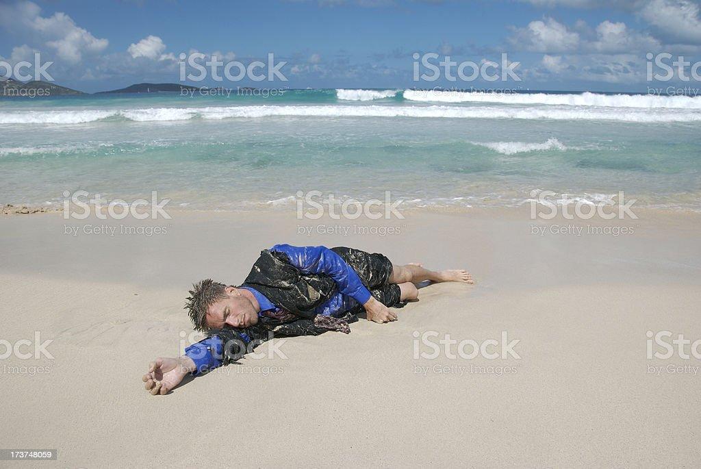 Beached Businessman Sleeps on Shore stock photo