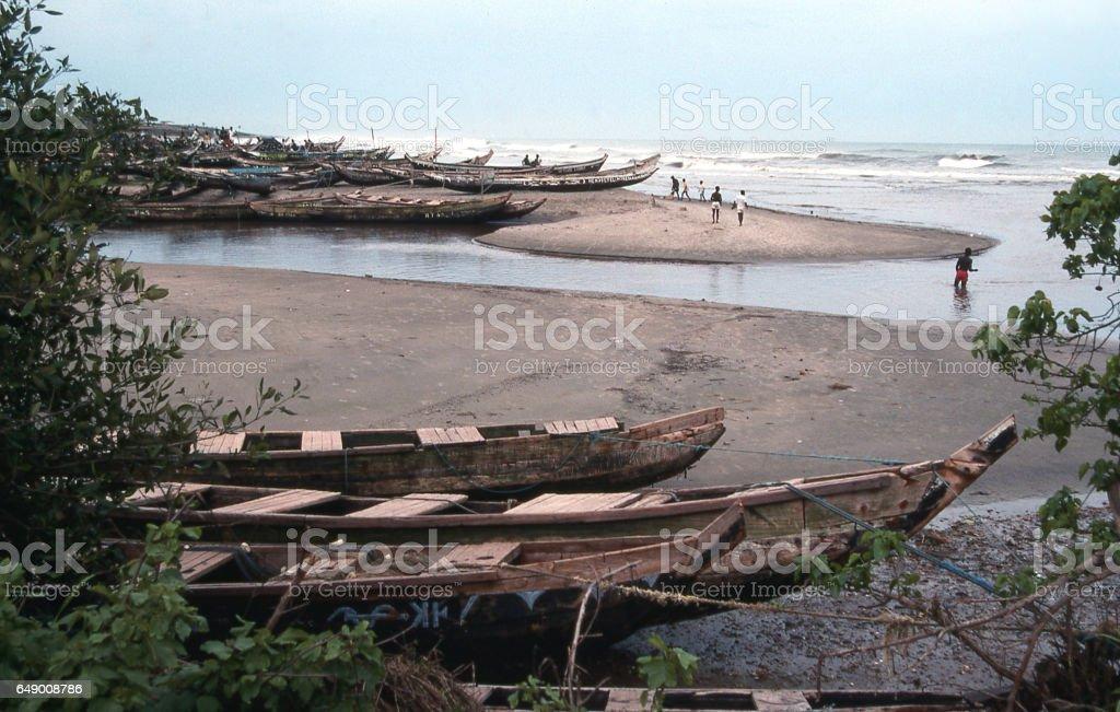 Beached fishing boats along creek entering Atlantic Ocean near Accra Ghana Africa stock photo