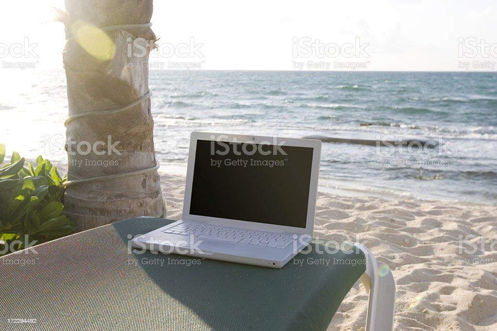 Beachfront Laptop on Sunny Tropical Beach, Nobody, Copy Space royalty-free stock photo