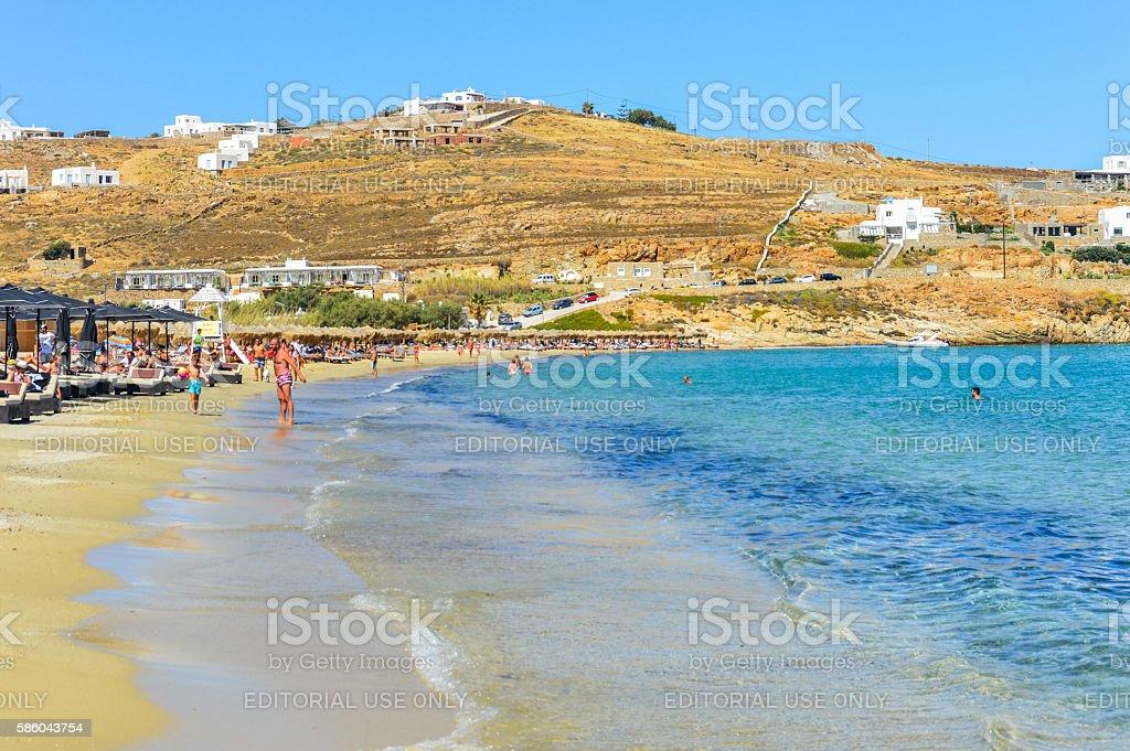 Beachgoers enjoy beautiful beach and tropical sea - Mykonos, Greece stock photo