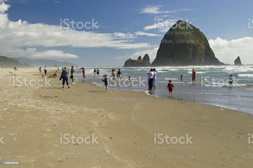 Beachgoers Playing At Cannon Beach With Haystack Rock, Oregon stock photo