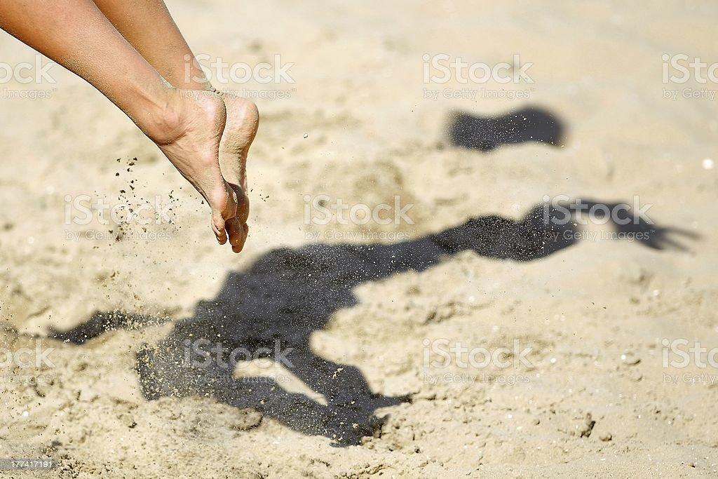 Beachvolleyball feet with shadow on the sand stock photo