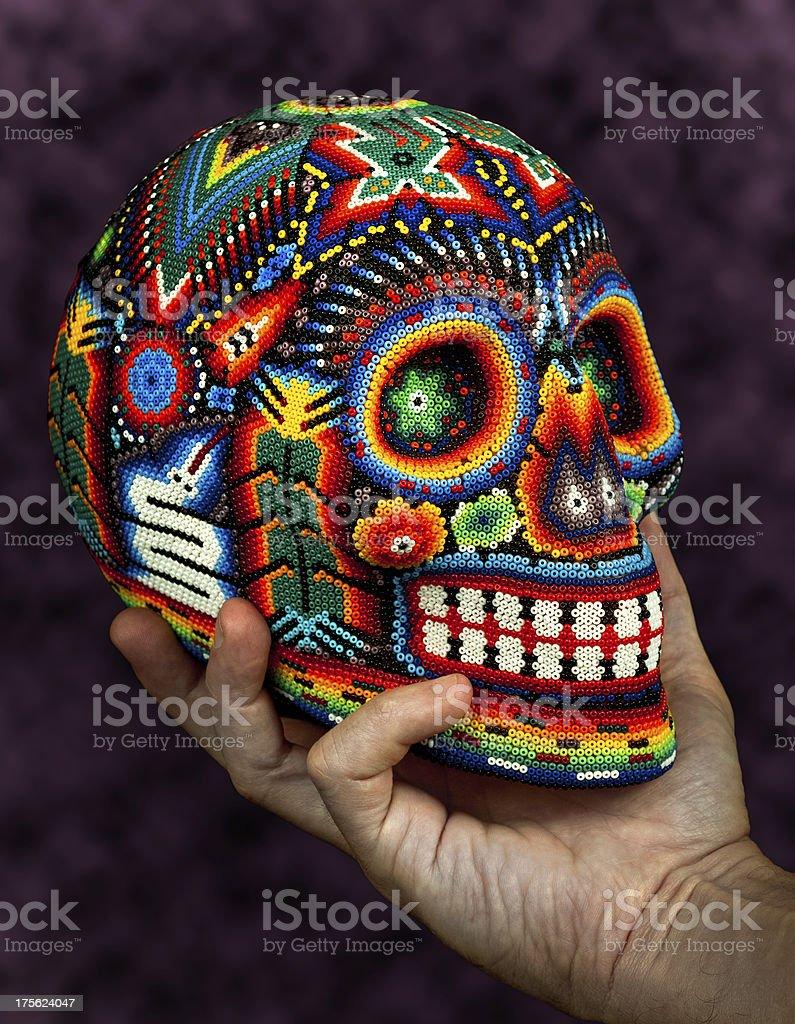 Beaded skull on hand stock photo