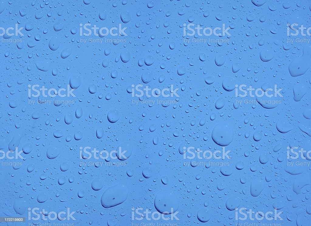 Beaded Water Drops on a Blue Surface royalty-free stock photo
