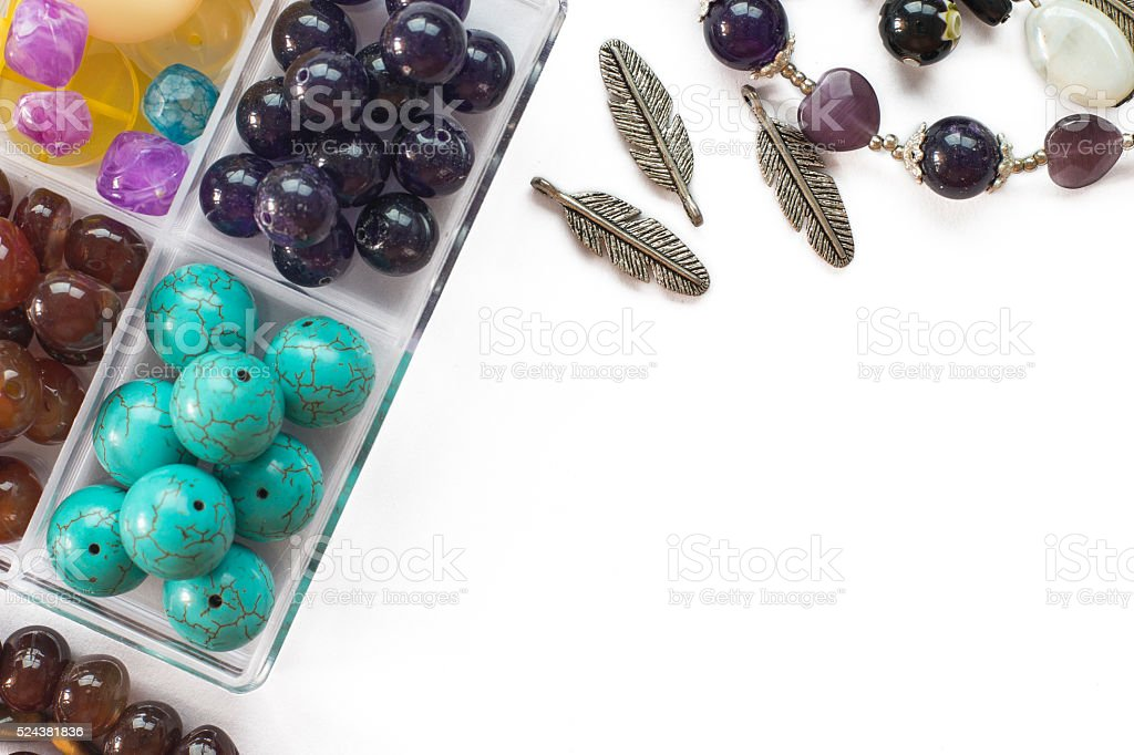 Beads and tools on white background flat lay stock photo