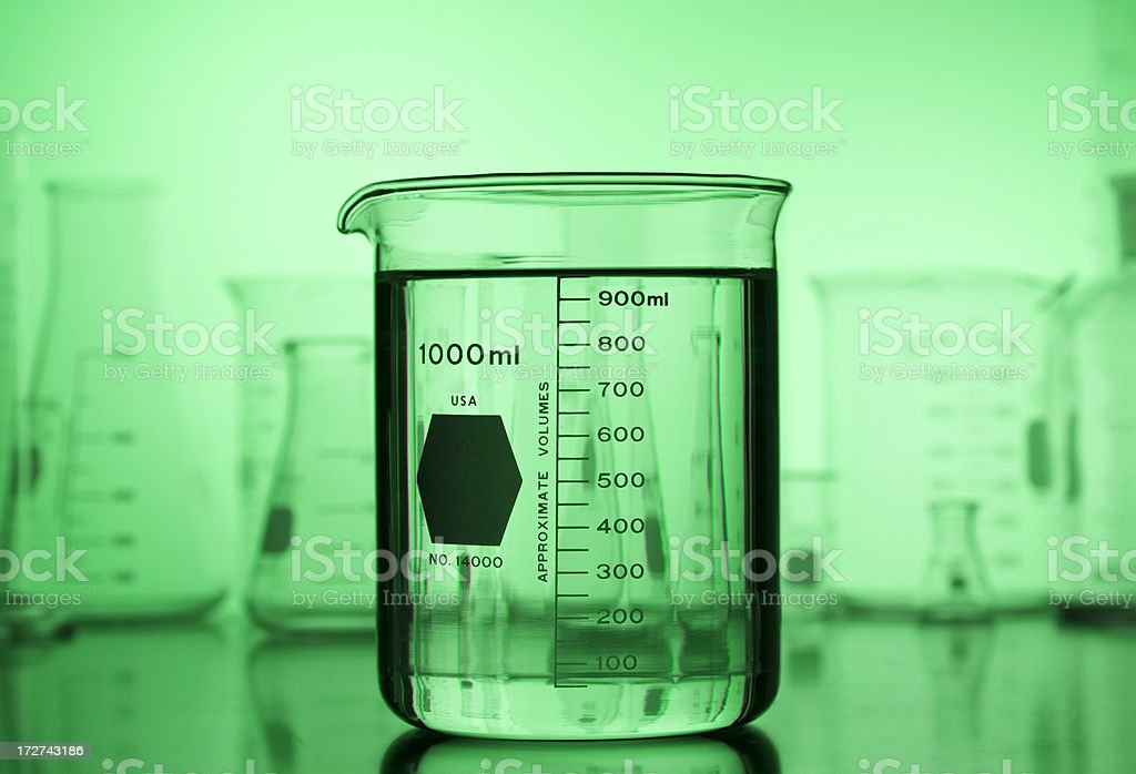 Beaker on Green Gradient with Lab Glass Background royalty-free stock photo