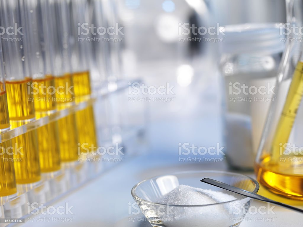 Beakers with amber colored liquid and white powder in a dish royalty-free stock photo
