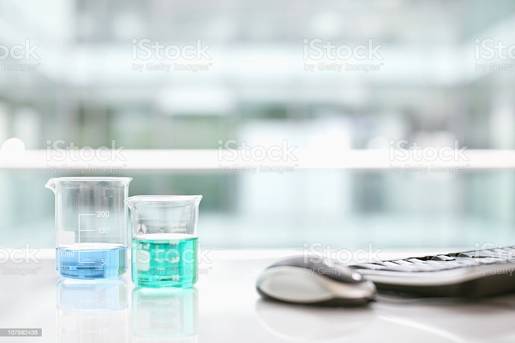 Beakers with computer mouse and keyboard on desk stock photo